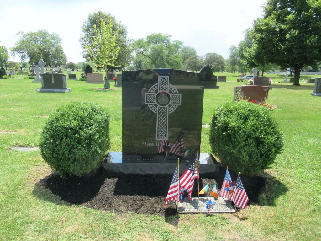Grave with two bushes on each side and American flags