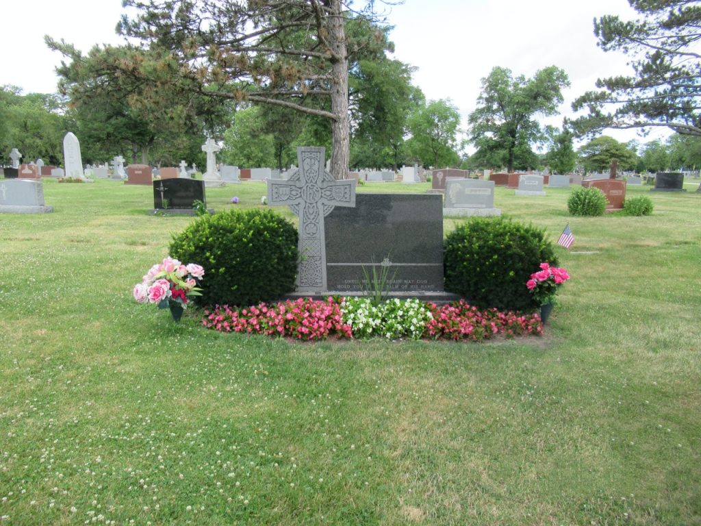 Gravesite with flowers and bushes around it.