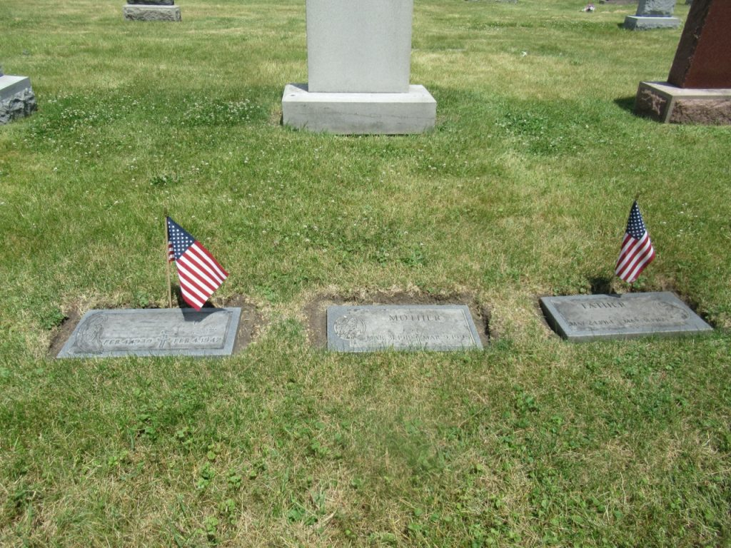 Gravesite with trimmed grass and American flags.