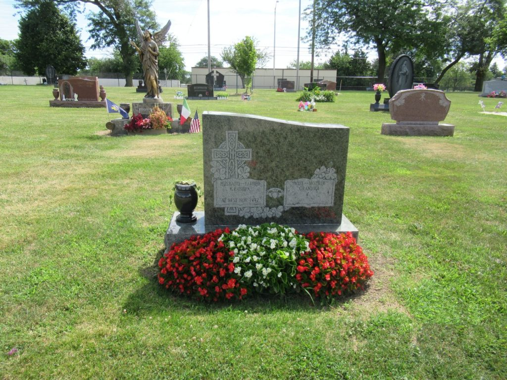 Grave site with flowers around it.