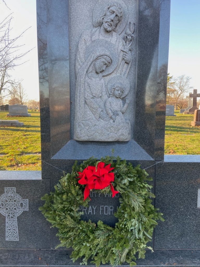 Christmas wreath with red bow in front of grave.